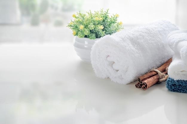 Oprollen van witte handdoeken op witte tafel met kopie ruimte op onscherpe woonkamer achtergrond.