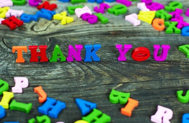 Opschrift dank aan u uit de veelkleurige houten kleine letters
