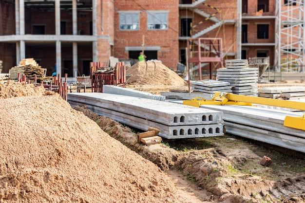 Opslag van materialen op de bouwplaats. gewapende betonnen platen voor de bouw. oprichting van een gebouw uit blokken.