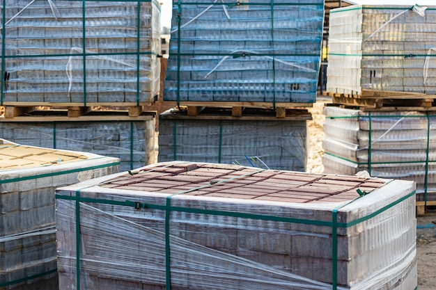 Opslag van straatstenen op pallets op de bouwplaats. kant-en-klare betonnen bestratingsplaten. afgewerkte producten magazijn.