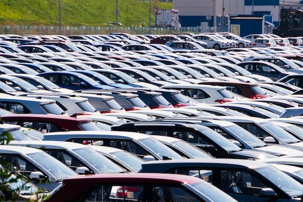 Opslagparkeerterrein van nieuwe onverkochte auto's. auto's van verschillende klassen en kleuren staan op de parkeerplaats