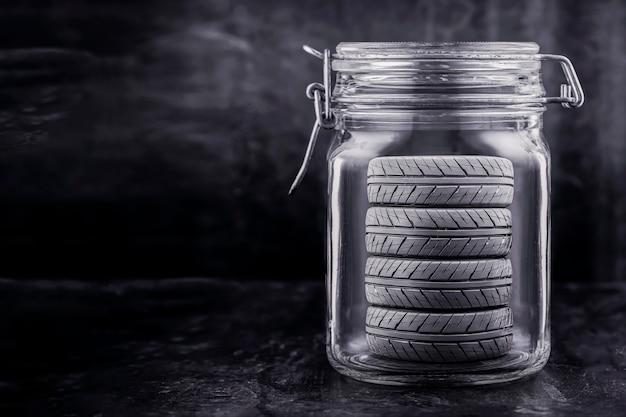 Opslagservice voor autobanden. wielen worden bewaard in een glazen pot, concept. kopie ruimte, zwarte achtergrond.