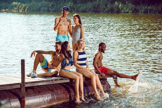 Opspattend water en lachend op de pier op de rivier