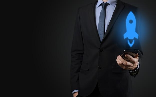 Opstart bedrijfsconcept, zakenman met tablet en pictogram raket lanceert en vliegt uit het scherm met netwerkverbinding op donkere achtergrond.