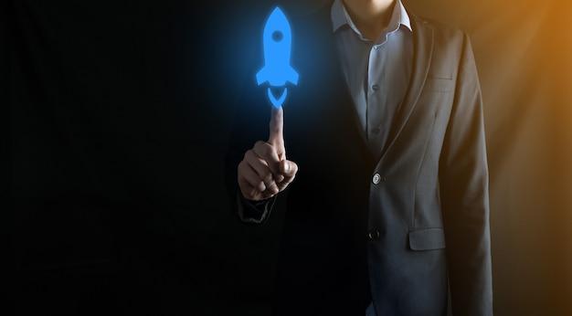 Opstart bedrijfsconcept, zakenman met tablet en pictogramraket lanceert en vliegt uit het scherm met netwerkverbinding op donkere muur.