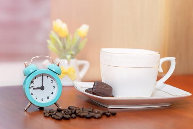 Opstartconcept. vintage wekker close-up begin van een goede dag met een kopje koffie en een bloempot op de achtergrond in de ochtendzon.