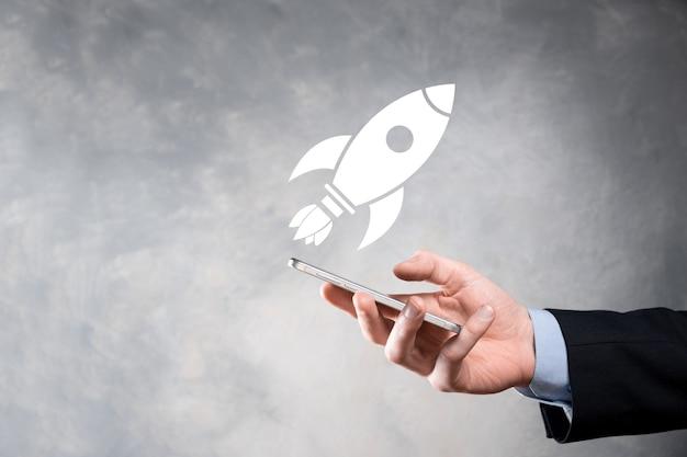 Opstarten bedrijfsconcept, zakenman met tablet en pictogramraket lanceert en vliegt uit het scherm met netwerkverbinding op donkere muur.