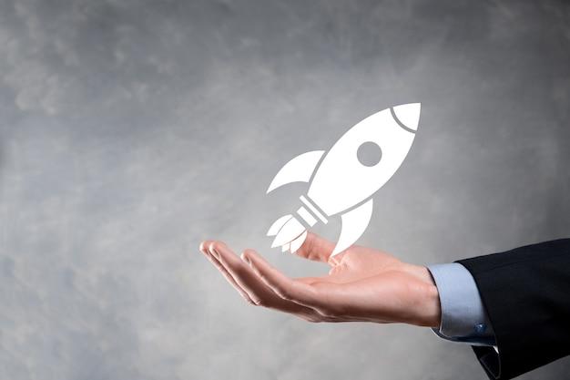 Opstarten bedrijfsconcept, zakenman met tablet en symboolraket lanceert en vliegt uit het scherm met netwerkverbinding op donkere muur.