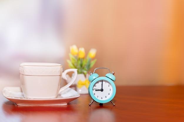 Opstarten concept. koffiekopje, vintage wekker, koffiedag in de ochtend.