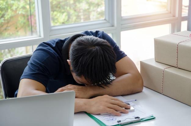 Opstarten. jonge man slapen en moe tijdens het werken aan bureau met laptopcomputer, klembord en levering pakketverpakking doos op tafel, kleine ondernemer thuis kantoor, verzending en mkb concept