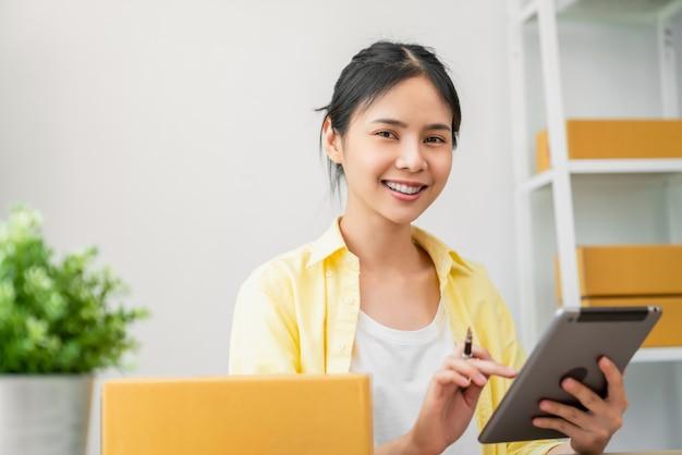 Opstarten klein bedrijf, een jonge aziatische vrouw die online bestelling op digitale laptop en verpakkingsdozen controleert