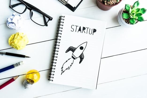 Opstarten van bedrijven met blocnote op bureautafel met benodigdheden en potcactus