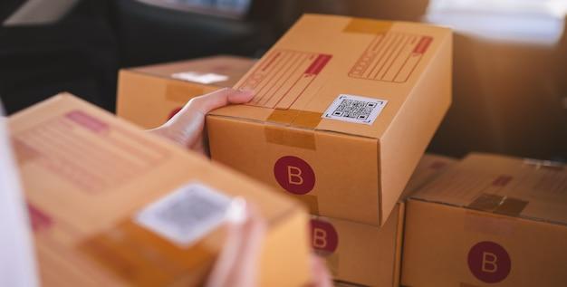 Opstarten van kleine bedrijven, handverpakkingsdozen voor producten om naar klanten te verzenden, werken op het thuiskantoor.