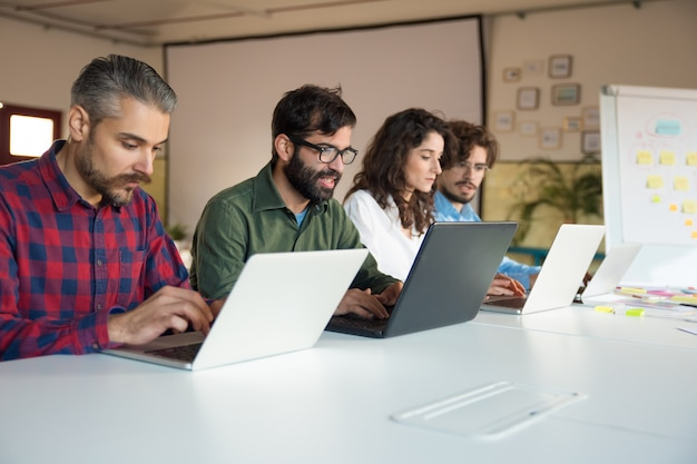 Opstartteam dat samenwerkt aan project, met behulp van laptops