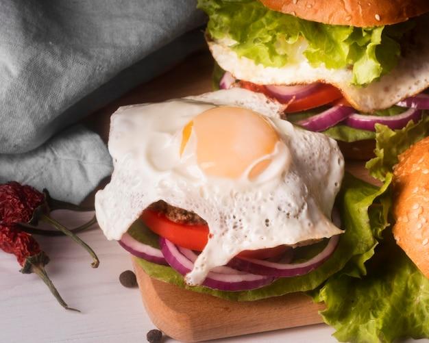 Opstelling van heerlijke hamburgers met gebakken ei