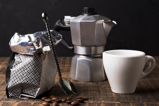 Opstelling van koffiemolen met zak en mok vooraanzicht