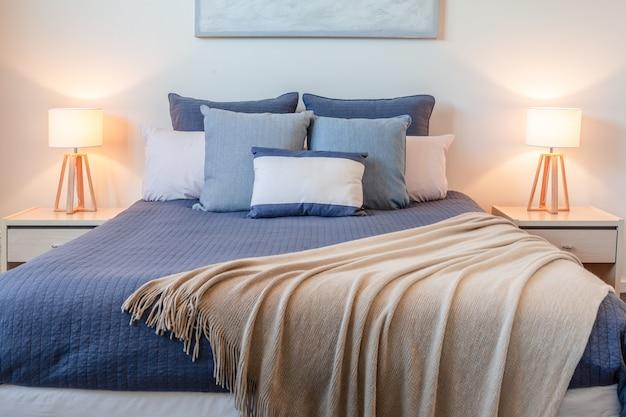 Opstelling van kussens op bed in een slaapkamer met bedlampjes