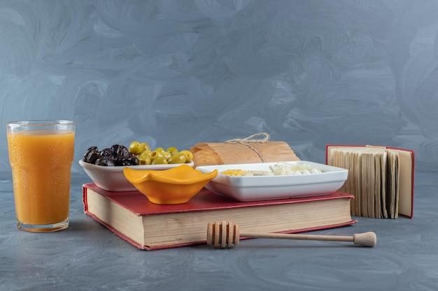 Opstelling van ontbijt en boeken over marmeren tafel.