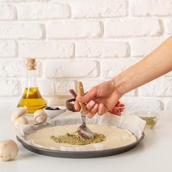Opstelling van smakelijke pizza in de maak