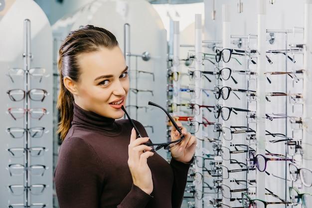 Optica close-up van een jong mooi meisje dat glazen draagt die dichtbij de tribune glimlachen