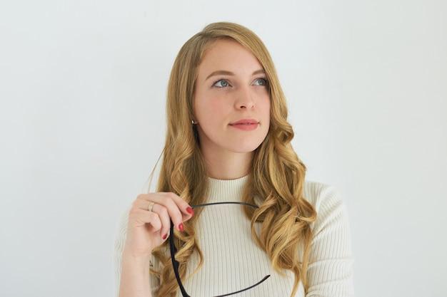 Optica stijl, schoonheid, mode, cosmetica en make-up concept. foto van succesvolle jonge blanke zakenvrouw met lang golvend haar opzoeken met doordachte uitdrukking, elegante bril te houden