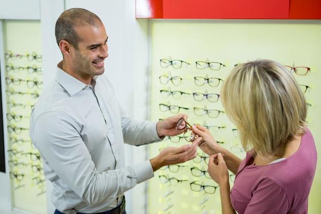 Opticien die klant helpt voor het selecteren van een brilmontuur