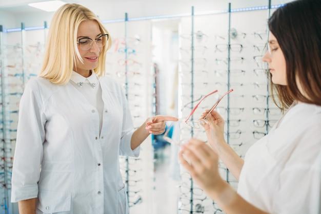 Opticien en koper tegen vitrine met bril
