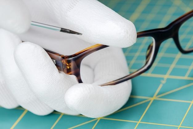 Opticien handen repareren in handschoenen bril met een gereedschap.