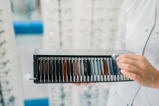 Opticien houdt doos met lenzen van verschillende kleuren