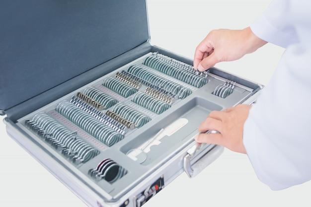 Opticien mannelijke handen kiezen lenzen uit een set corrigerende lenzen