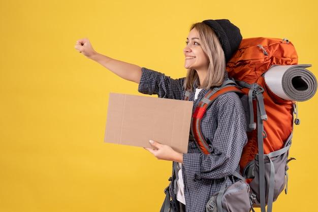 Optimist reiziger vrouw met rugzak met karton
