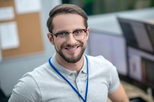 Optimist. tevreden lachende donkerharige jonge volwassen man met bril op kantoor tijdens het werken