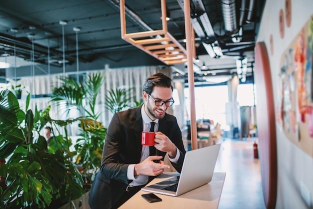 Optimistisch aantrekkelijk kaukasisch bebaarde zakenman in pak en met bril mok met koffie te houden en te wijzen op laptop terwijl staande aan de balie. bedrijf interieur.