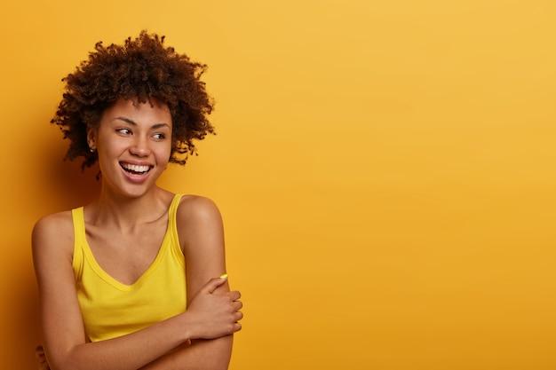 Optimistisch blij duizendjarig meisje kruist handen, staat verlegen en drukt positieve gevoelens uit
