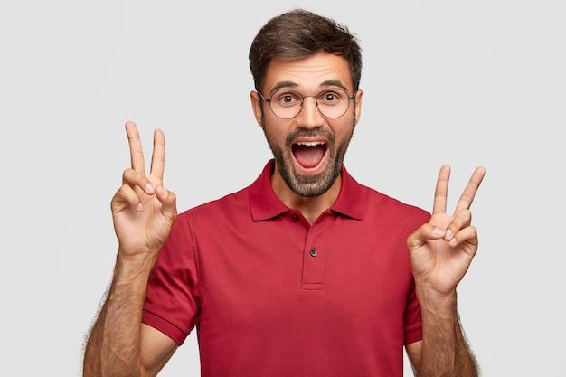 Optimistisch blij ongeschoren man met positieve gezichtsuitdrukking, toont v-teken of overwinningsgebaar met beide handen
