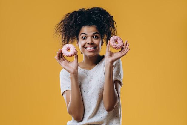Optimistisch blije vrouw met donkere huidskleur met afro-kapsel, heeft twee zoete, donuts met glitters, heeft plezier met snoep, nonchalant gekleed