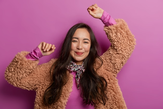 Optimistisch donkerharig meisje houdt de armen omhoog, heeft een ontspannen, gelukkige uitdrukking, viert de overwinning, juicht over de paarse ruimte, heeft plezier