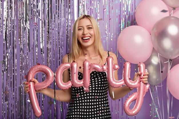 Optimistisch gelukkig blonde vrouw draagt modieuze polka dot jurk, maakt foto met ballonnen op feestje