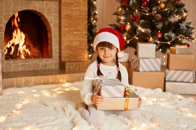 Optimistisch klein kind met witte trui en kerstmuts, zittend op zacht tapijt met stapel huidige dozen, poserend in feestelijke kamer met open haard en kerstboom.