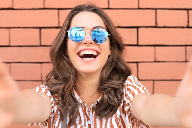 Optimistisch lachend meisje poseren voor oude muur achtergrond.