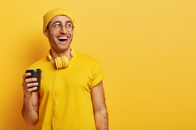 Optimistisch man in glazen lacht als tijd doorbrengt met vrienden tijdens koffiepauze, wegwerpbeker houdt, wegkijkt