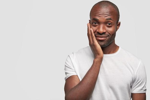 Optimistisch opgetogen afro-amerikaanse jonge man kijkt gelukkig en houdt de hand op de wang