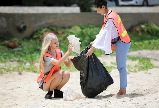 Optimistisch twee vrijwilligers die een vuilniszak vasthouden en helpen bij het ophalen van afval in het park, ze halen het afval op en stoppen het in een zwarte vuilniszak.