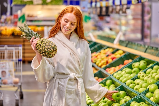 Optimistisch vrouw fruit kopen, ananas en appels kiezen, het dragen van badjas, glimlachend