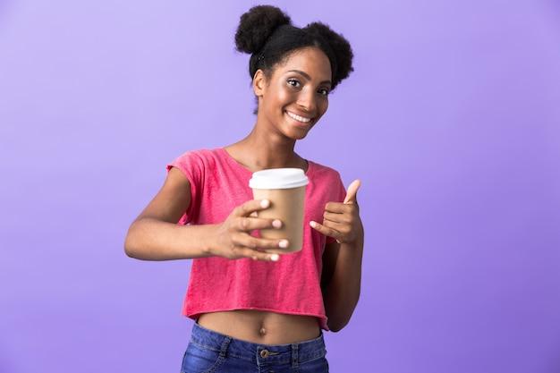 Optimistische afro-amerikaanse vrouw in casual kleding met papieren beker met afhaalmaaltijden koffie, geïsoleerd