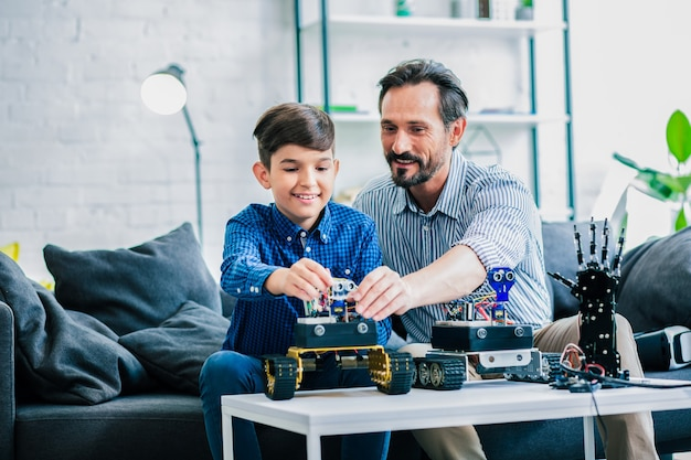 Optimistische bebaarde man en zijn zoon zitten aan tafel terwijl ze betrokken zijn bij robottechnologie