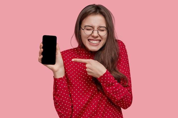 Optimistische blanke vrouw wijst naar nieuwe slimme telefoon voor reclame, toont een leeg scherm, houdt van multifunctionele gadget