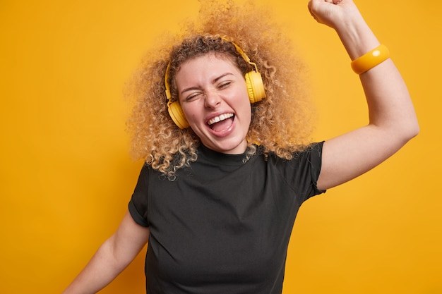 Optimistische blije europese vrouw met krullend haar heeft plezier, steekt armen op en heeft een vrolijke stemming, luistert naar favoriete muziek uit een afspeellijst die over een levendige gele muur is geïsoleerd. dolblij tienermeisje dwaast rond