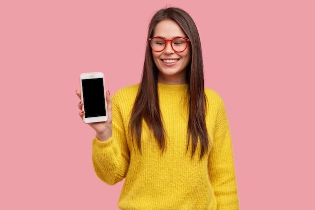 Optimistische brunette dame toont smartphonescherm, verheugt zich over het kopen van nieuwe gadget, draagt een bril en een gele trui
