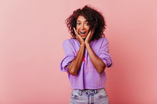 Optimistische brunette vrouw haar gezicht aan te raken. indoor portret van modieus afrikaans meisje geïsoleerd op pastel.